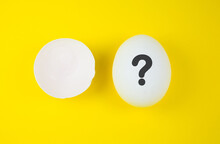 White Egg With Question Mark And Eggshell On The Yellow Background. Pregnancy And Baby Concept. Who Is? Copy Space. Minimalism, Original And Creative Photo. Beautiful Wallpaper. Easter Holidays.