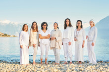 Group Portrait Of Beautiful Women Posing Outside With Beautiful Mountain Landscape On Background, Wearing White Clothes