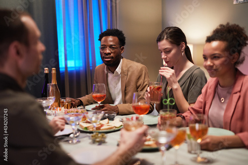 Diverse group of young people sitting at dinner table while enjoying party indoo Fototapet