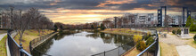 A Stunning Panoramic Shot Of A Still Lake With An Iron Bridge And A Fountain In The Middle Of The Lake With Green And Autumn Colored Trees And Plant At The Commons Park In Atlanta Georgia