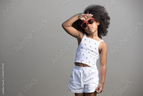 Photo childhood and emotion concept - little african american curly hair girl  wearing red sunglasses and dancing hiphop