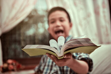 A Boy Giving Books To Camera