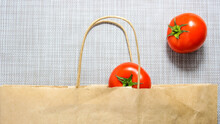Tomatoes That Are Put In A Paper Shopping Bag.