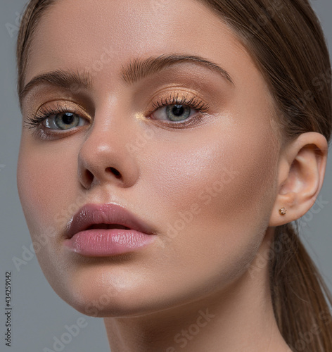 Close-up of a woman's face. The beauty. Clean healthy skin. Golden eyeshadow. Female portrait.