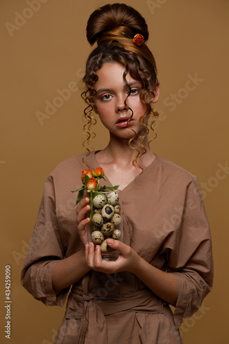 Portrait of a teenage girl. In the hair of the rose. She is holding a glass with sawn eggs and a bouquet of flowers in her hands. Unusual hairstyle.