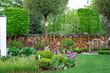 Nowoczesny piękny ogród z angielską ławeczką na tle drewnianego ogrodzenia. Dom z nowoczesnym ogrodem . Miejsce do wypoczynku