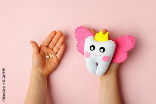 Fotografia Felt tooth fairy pillow and milk tooth in kids hands on pink background with copy space for text