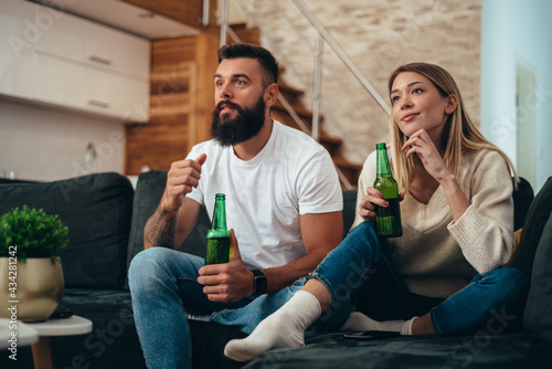 Foto Young beautiful couple drinking beer and watching sport game on a television at