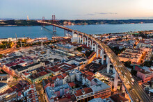 Aerial View Of April 25th Bridge With Christ The King Statue (Cristo Rei) In Background At Sunset, View Of Lisbon Skyline At Night, Alcântara, Lisbon, Portugal.