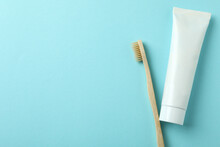 Eco Friendly Toothbrush And Tube Of Toothpaste On Blue Background
