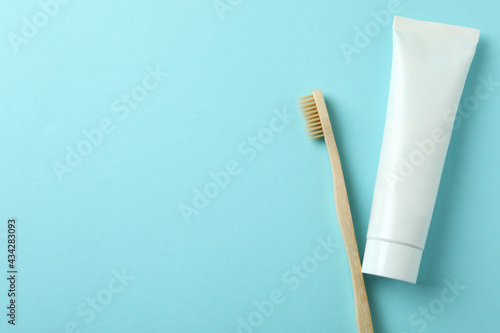 Fotografiet Eco friendly toothbrush and tube of toothpaste on blue background