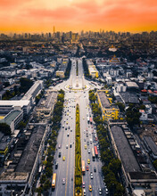 Aerial View Of A Large Road With A Monumental Roundabout With Skyline In Background At Sunset, Bangkok, Thailand.