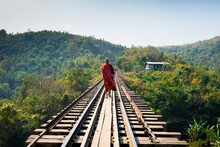 Rear View Of Monk Walking On Railroad Track