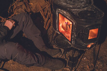 Camping In Winter. Warming Up With A Wood Stove On A Cold Night.