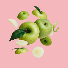 Green Apple Slices Flying And Levitating On The Pastel Pink Background. Creative Fruit Concept. Minimal Food Poster For Vitamins, Healthy Diet Or Organic Cosmetics.