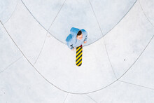 Aerial Top Down View Of Skateboarder Standing On Concrete Surface In Urban Skatepark, Kaunas, Lithuania.