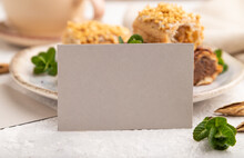 Gray Paper Business Card And Set Of Eclair On Gray Concrete Background. Side View Side View, Close Up.