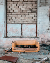 Abandoned Sofa Against Brick Wall Of Old Building