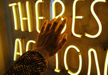 Close-up Of Hand Touching Illuminated Text At Night