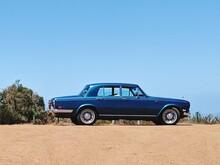 Vintage Car On Field Against Clear Blue Sky