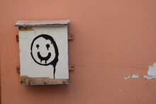 Close-up Of Information Sign And Smily On Wall