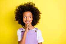 Photo Of Cunning Playful Small Girl Finger Chin Look Side Empty Space Wear Violet Overall Isolated Yellow Color Background