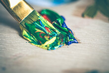 High Angle View Of Multi Colored Paintbrush And Paint On Table
