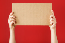 Hands Holding A Blank Sheet Of Cardboard On A Red Background.