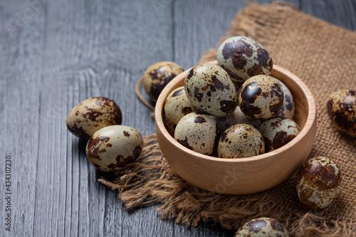 Fototapeta fresh quail eggs on the dark wooden background.
