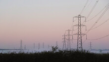 Low Angle View Of Electricity Pylons On Field Against Sky During Sunrise
