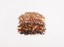 Set Of Crushed Makeup Products On White Background. Eye Shadows Neutral Beige And Brown Colors, Texture. Top View