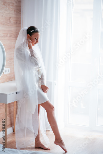 Fotografering Bride in wedding robe and veil leaning on dressing table