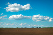 Preparing field for planting. Plowed soil in spring time and blue cloudy sky.