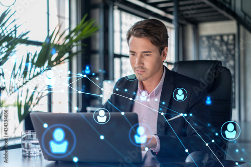 Handsome businessman in suit at workplace working with laptop to hire new employees for international business consulting Fototapeta