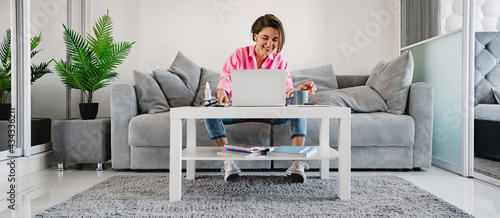 woman in pink shirt sitting relaxed on sofa at home at table working online on laptop