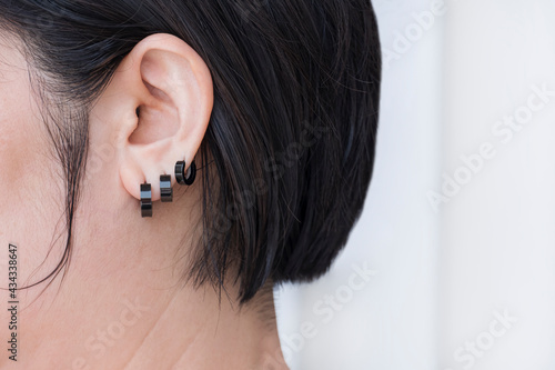 Fotografering Close up and side view of Bob hair woman wearing 3 black stainless steel earring