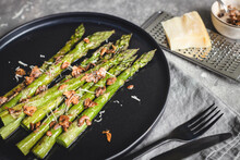 Baked Asparagus With Almond Nut Petals And Cheese On Black Plate.