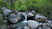 Beautiful View Of A Small Waterfall Among Huge Rocks
