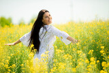 Young woman in the rapeseed field - 434358650