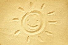 Sun Drawn In Sand With A Smiling Face