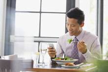 Businessman Looking At Smart Phone While Dining Out