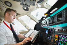 Male Pilot Checking Logbook In Airplane Cockpit