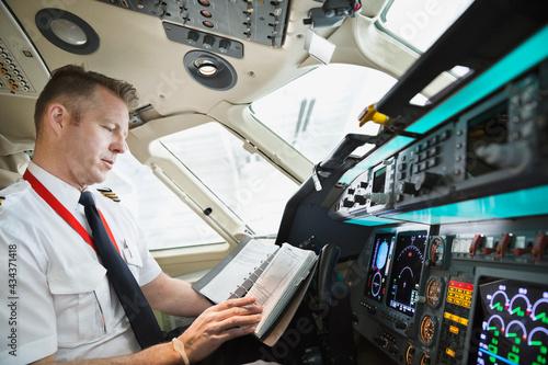 Fényképezés Male pilot checking logbook in airplane cockpit