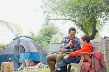 Father And Son Enjoying Hot Chocolate While Camping In Backyard