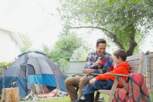 Papel de parede Father and son enjoying hot chocolate while camping in backyard