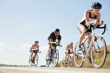 Group Of Triathletes Cycling On Street