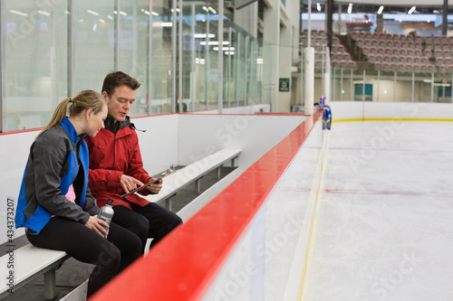 Foto Female figure skater with coach discussing routine in skating rink