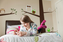 Young Girl With Headphones Listening To Music On Bed