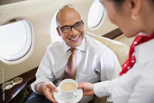 Fotografia Flight attendant serving coffee to businessman in private jet