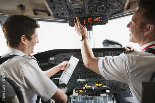 Pilot and copilot checking control panel in airplane cockpit Tapéta, Fotótapéta